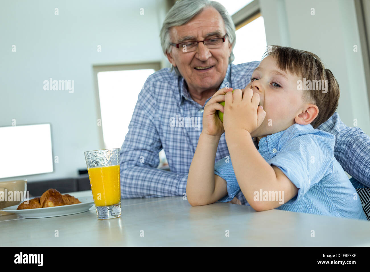 Grandfather and grandson having breakfast Stock Photo