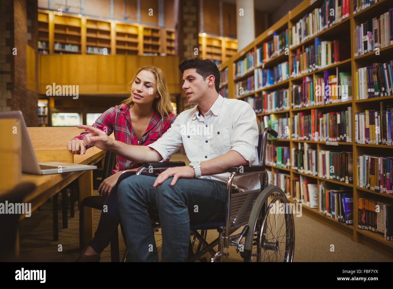 Student in wheelchair working with a classmate - Stock Image