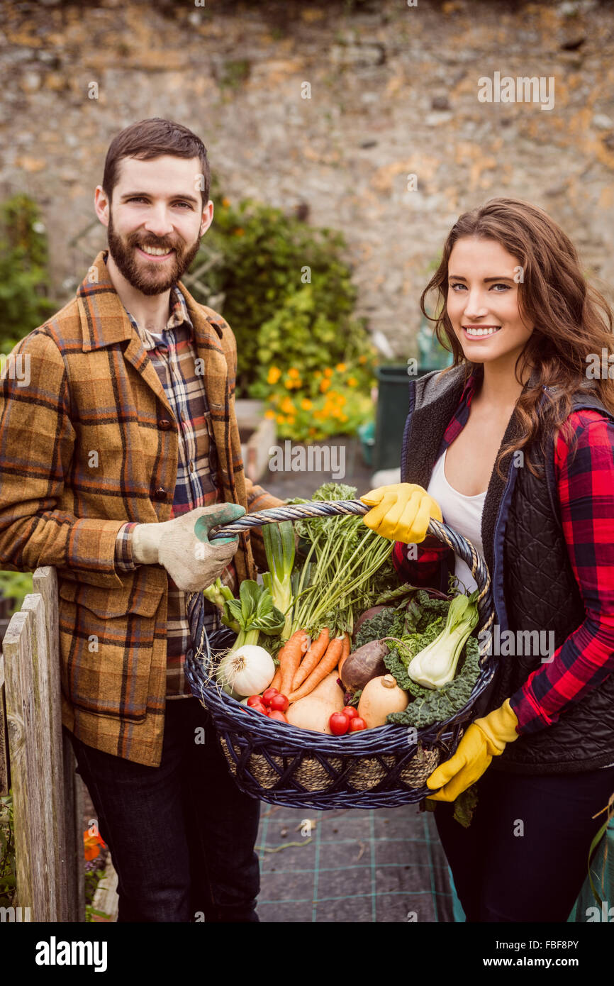 Proud couple showing basket of vegetables - Stock Image