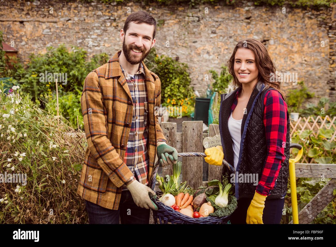 Proud couple showing basket of vegetable - Stock Image
