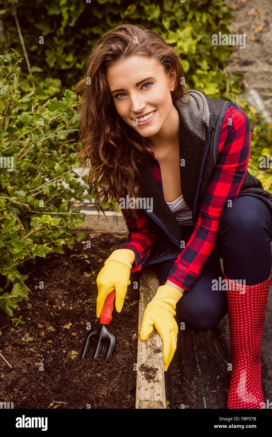 Smiling woman gardening with a trowel - Stock Image