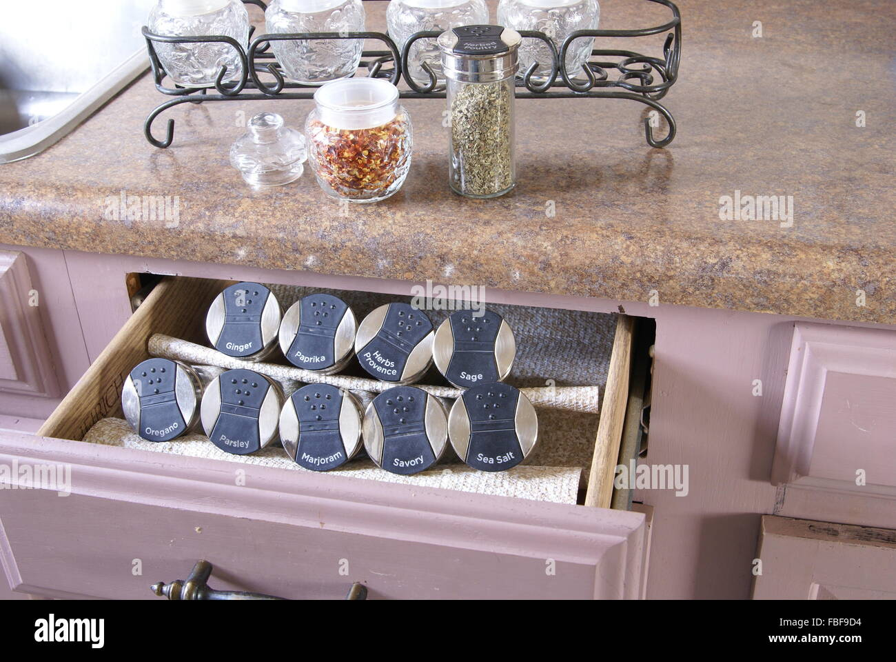 Labeled spice jars organized in a drawer - Stock Image