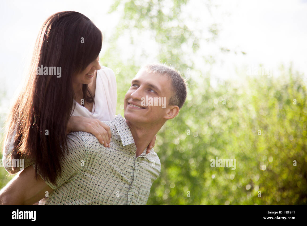 Couple in love on a date, young man giving his beautiful girlfriend piggyback ride, happy smiling, having fun together, - Stock Image