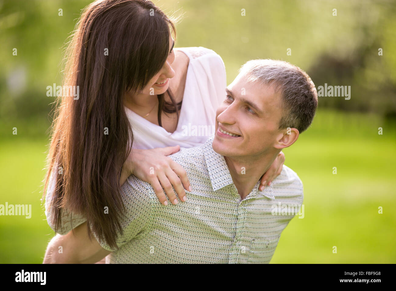 Portrait of happy young man and woman in love on a date, boyfriend giving his beautiful girlfriend playful piggyback - Stock Image