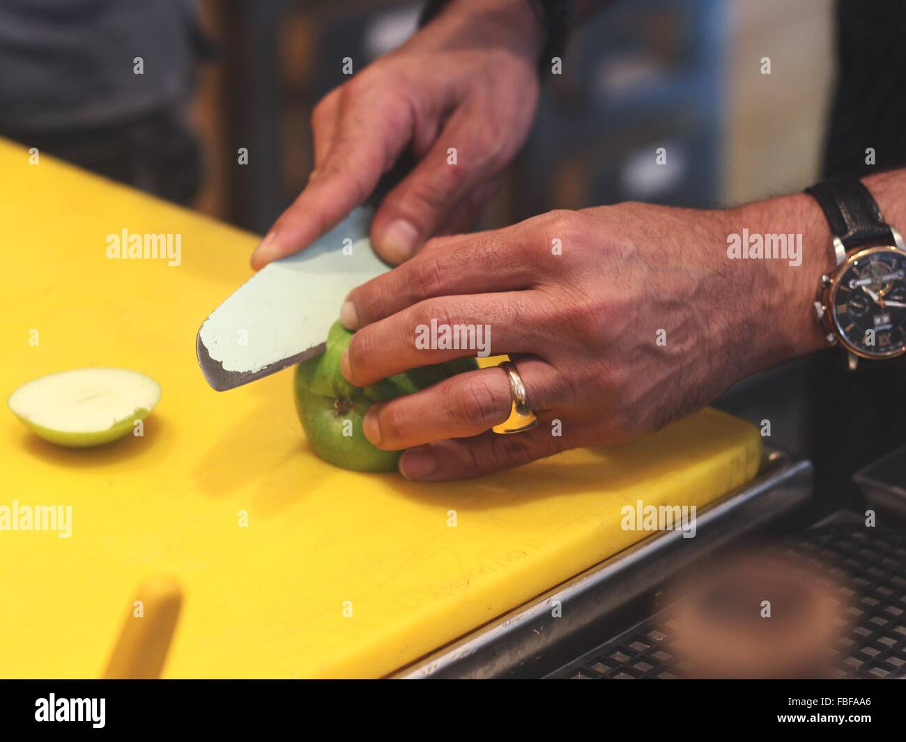 Cropped Image Of Chef Cutting Apple With Knife - Stock Image