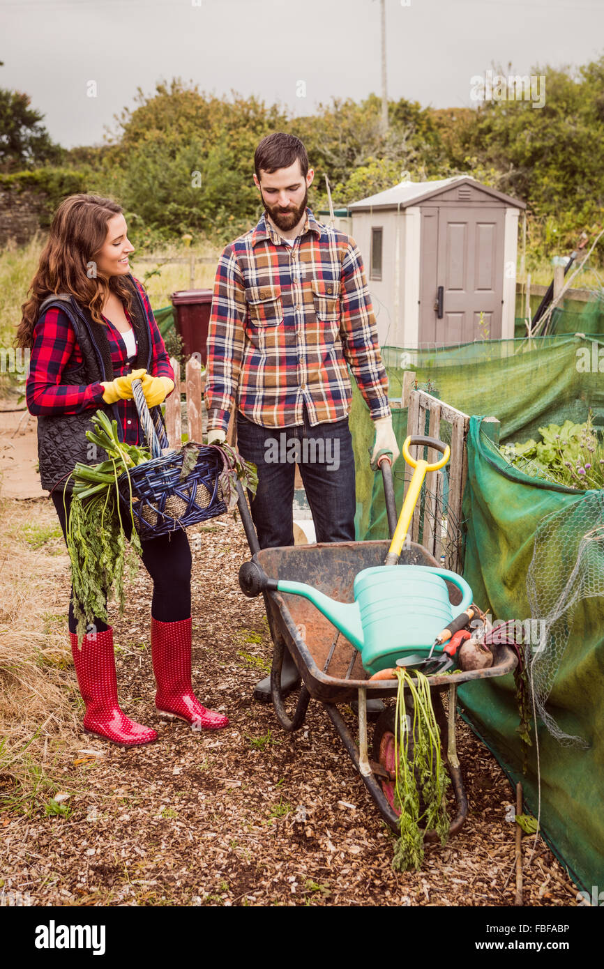 Couple with basket of vegetables and wheelbarrow - Stock Image