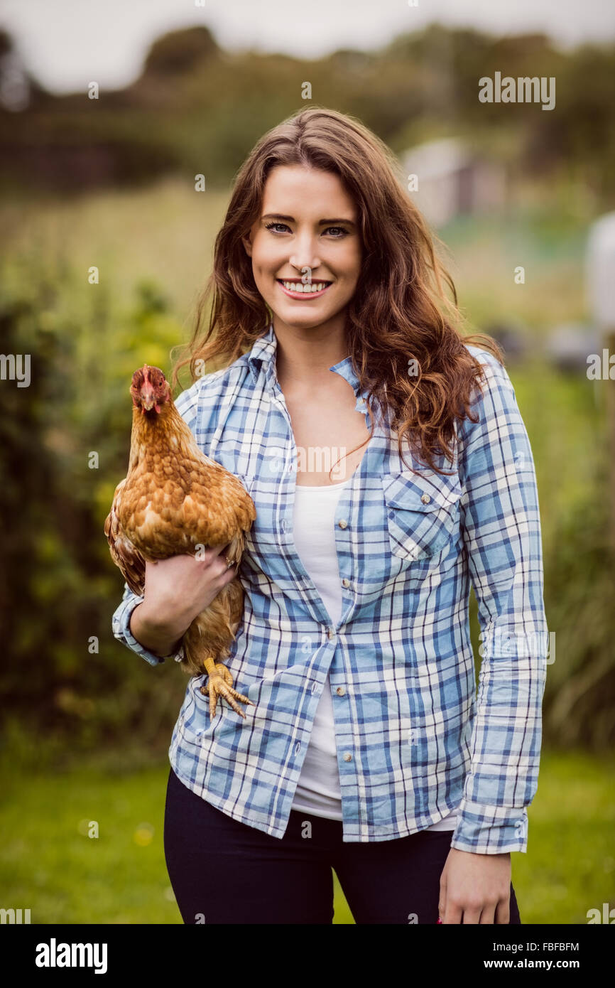 Smiling woman holding chicken - Stock Image