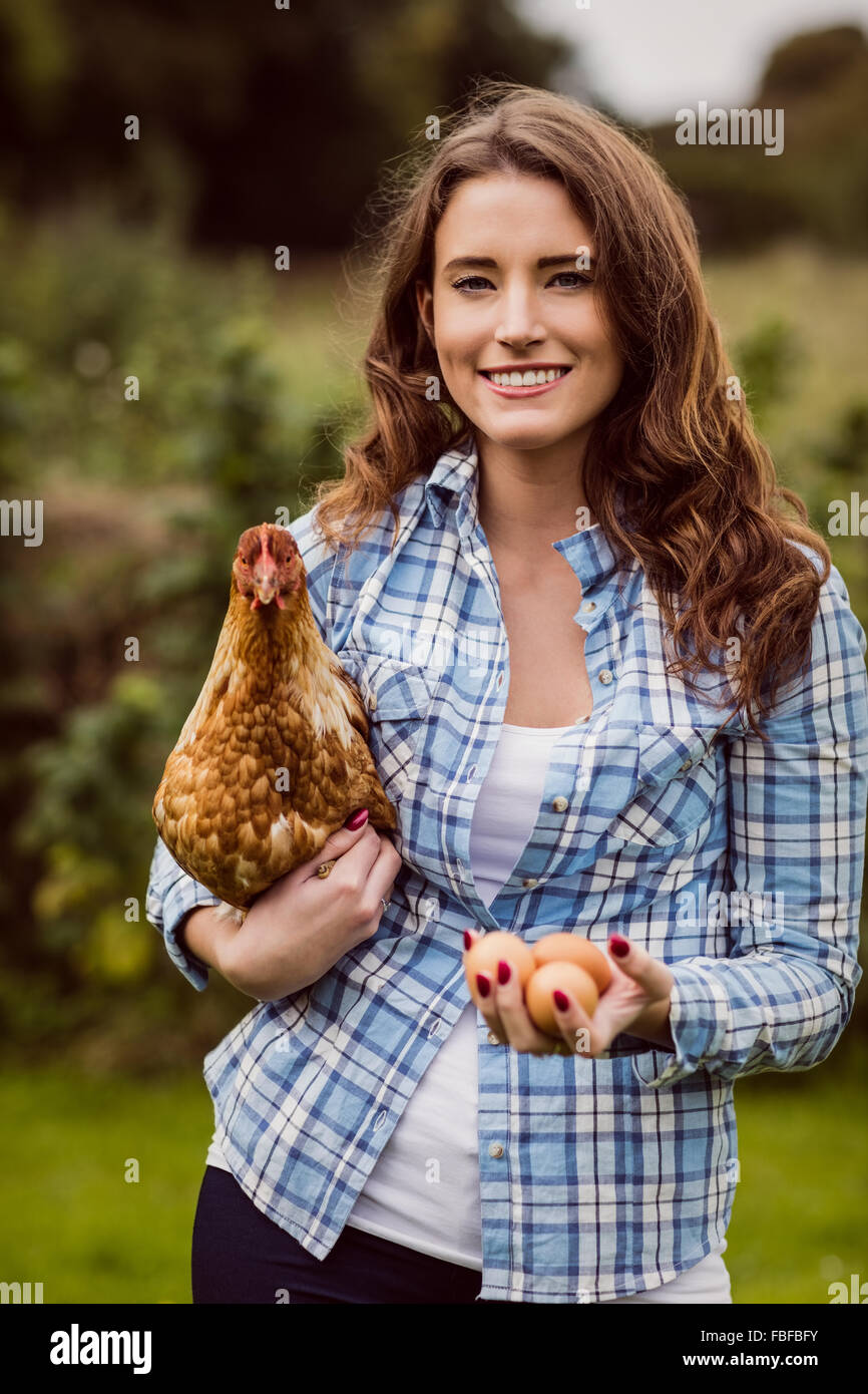 Woman holding chicken and egg - Stock Image