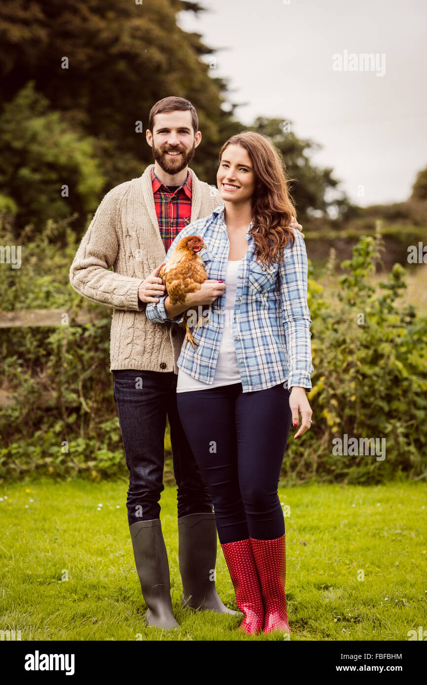 Smiling couple holding chicken - Stock Image