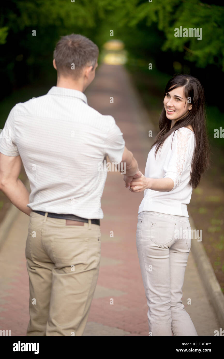 Young brunette woman in white jersey and jeans leading her lover by hand in park, looking at him, playfully laughing, - Stock Image