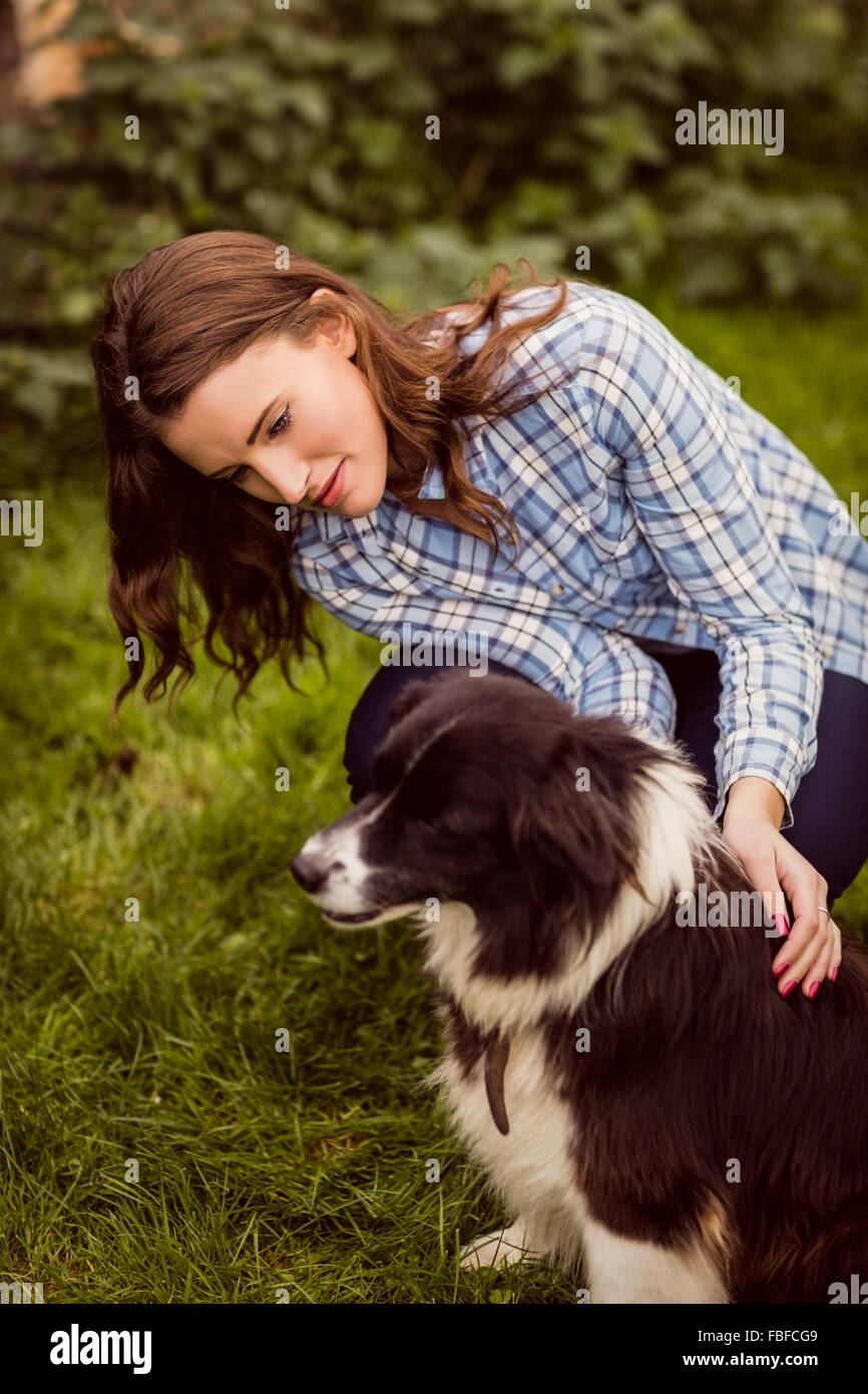 Young woman rubbing dog - Stock Image