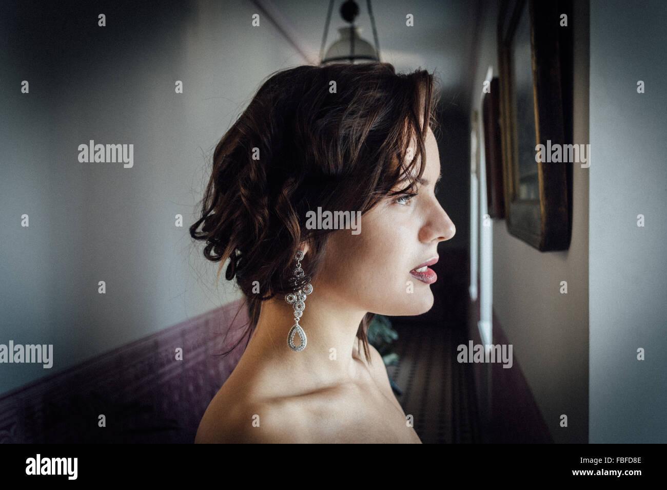 Profile View Of Thoughtful Beautiful Woman In Corridor - Stock Image