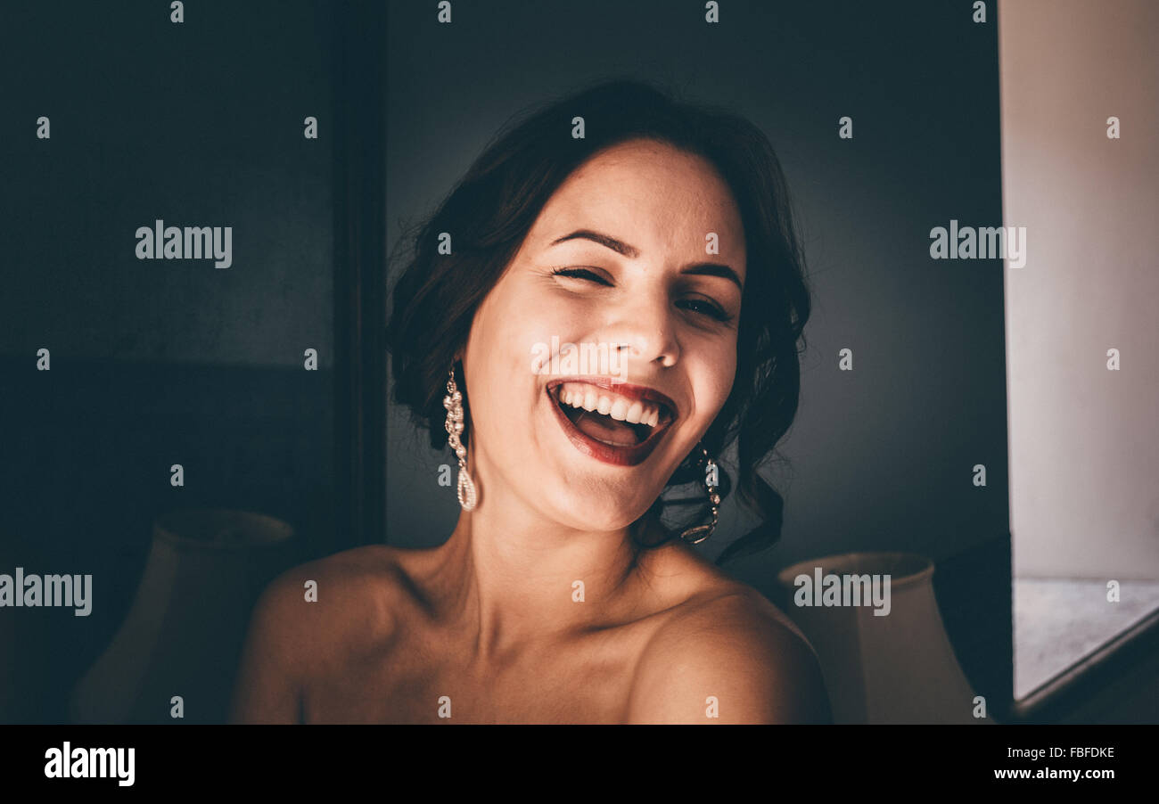 Portrait Of Young Cheerful Woman Winking At Home - Stock Image