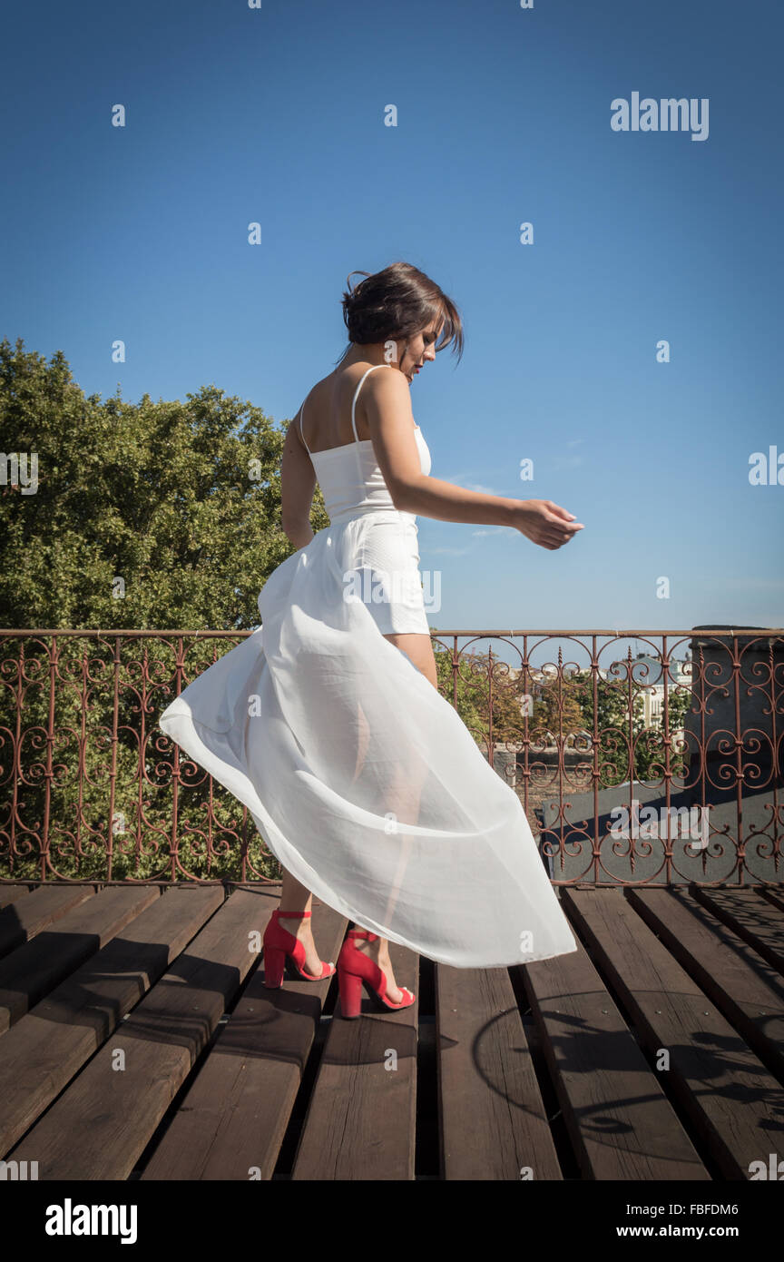 Young Woman In High Heels Dancing On Rooftop - Stock Image