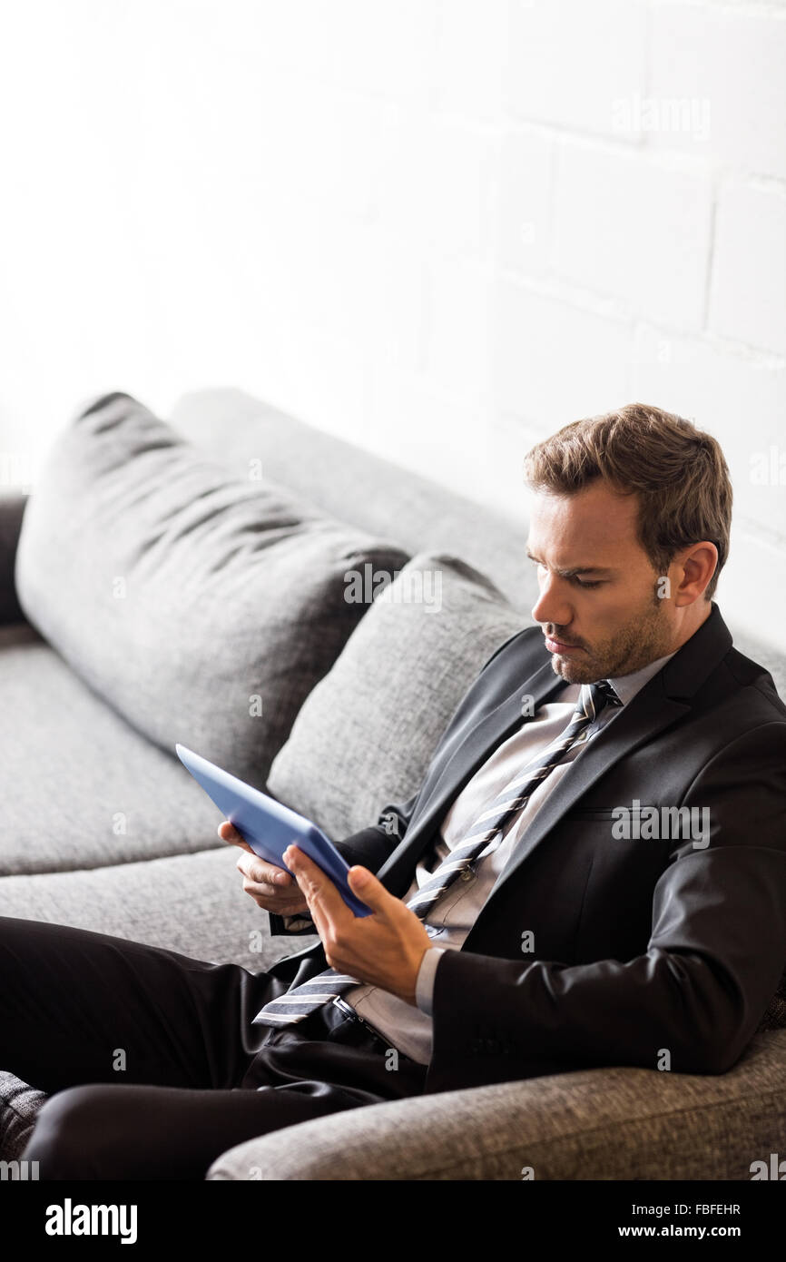 Focused businessman using tablet - Stock Image