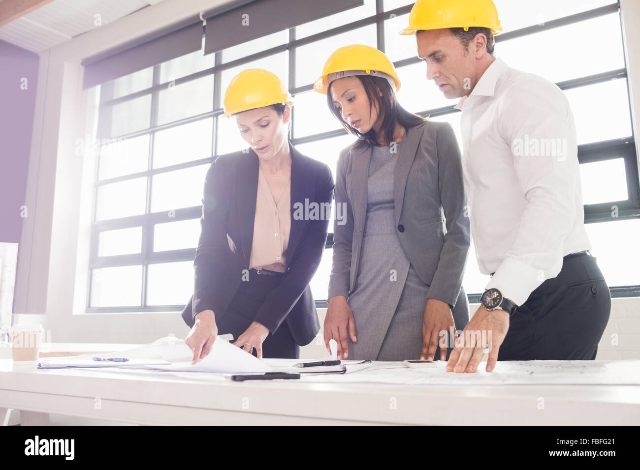 Business people wearing safety helmets - Stock Image