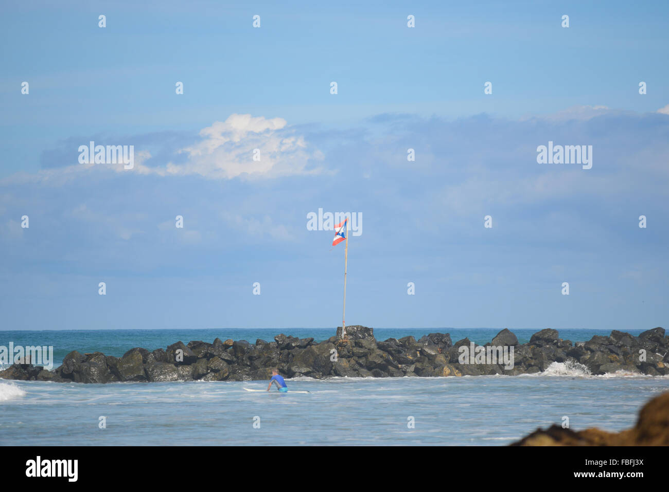Puertorican Flag Waving At Domes Beach Detail Of Surfer In The Water Rincon Puerto Rico USA Territory Caribbean Island