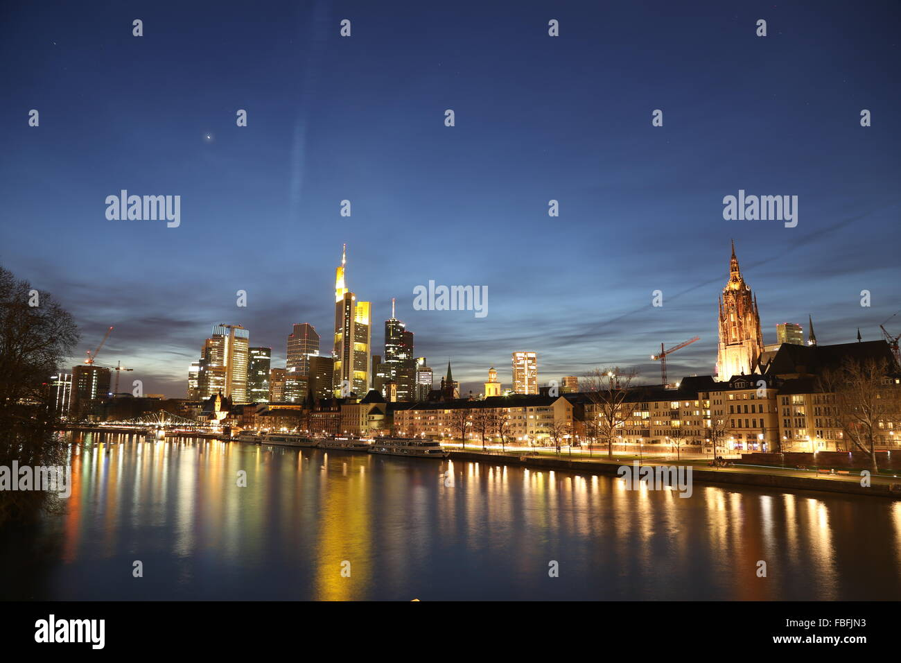 River By Illuminated Commerzbank Tower And City Against Sky At Night Stock Photo