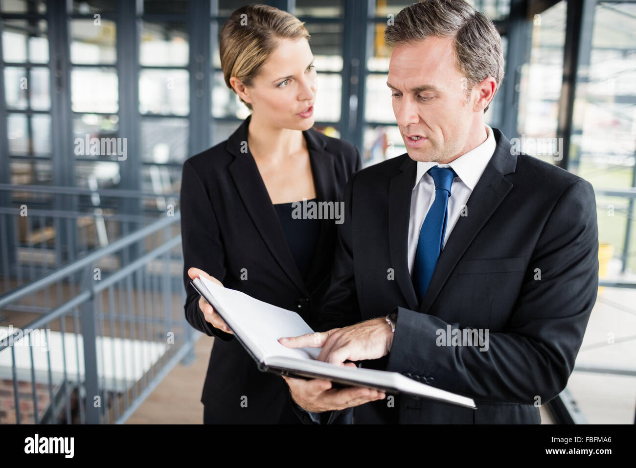 Business people discussing about a file - Stock Image