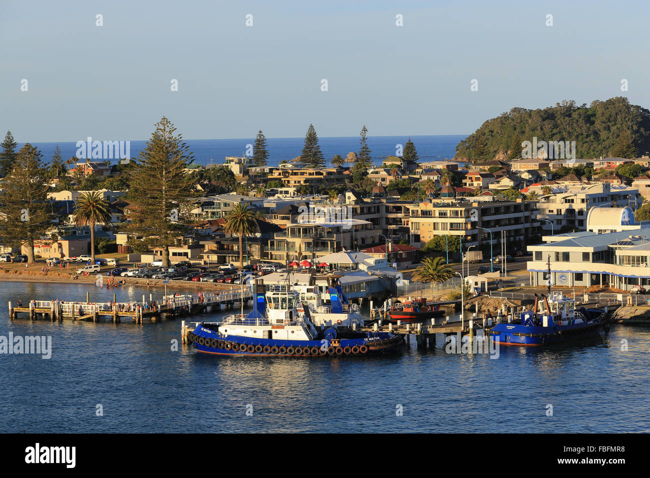 Tug boats and people along the waterfront at the Port of Tauranga in New Zealand. - Stock Image