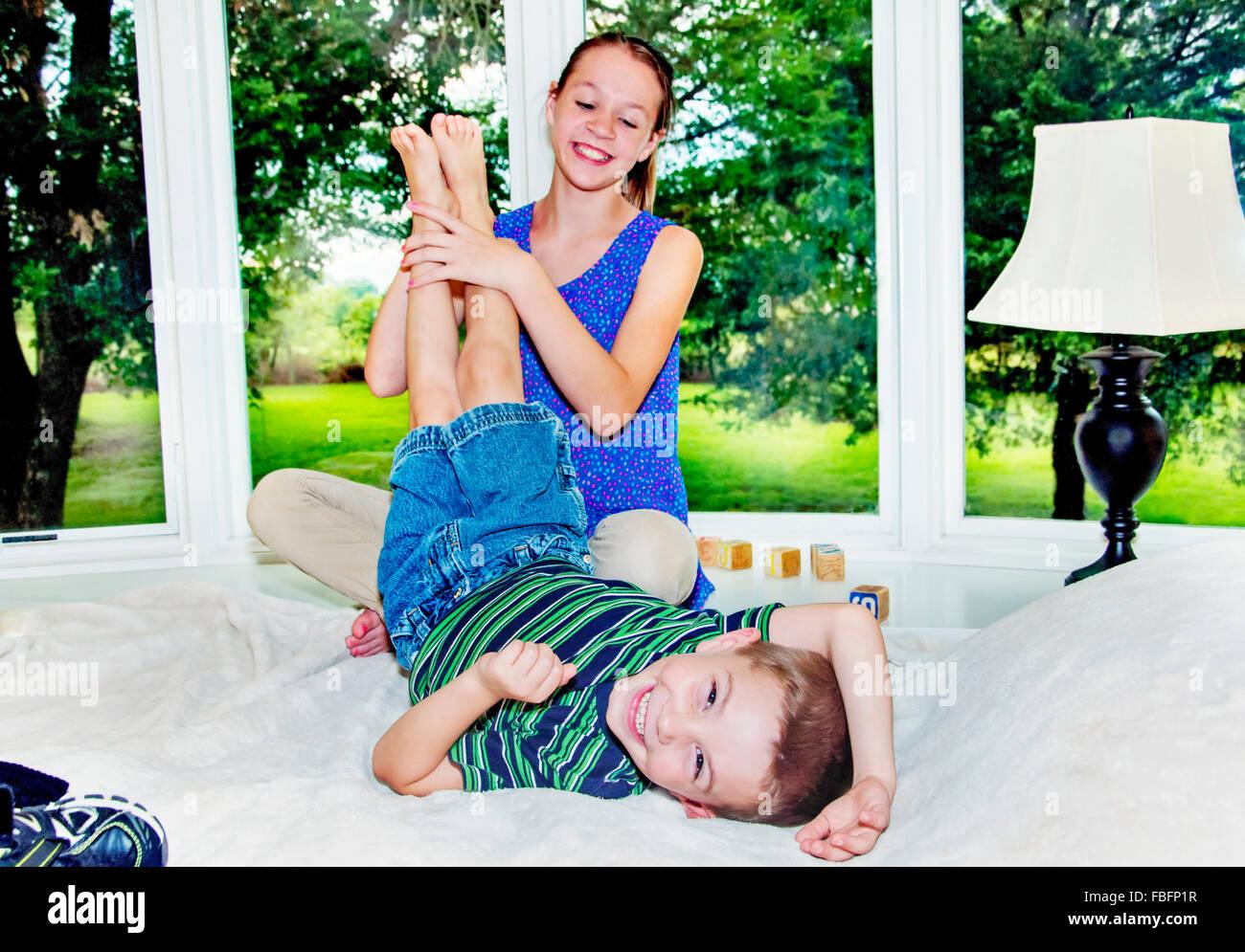 girl tickling little boys feet on bed - Stock Image
