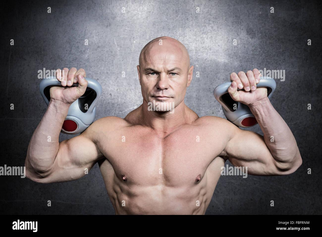 Composite image of portrait of bodybuilder lifting kettlebells - Stock Image