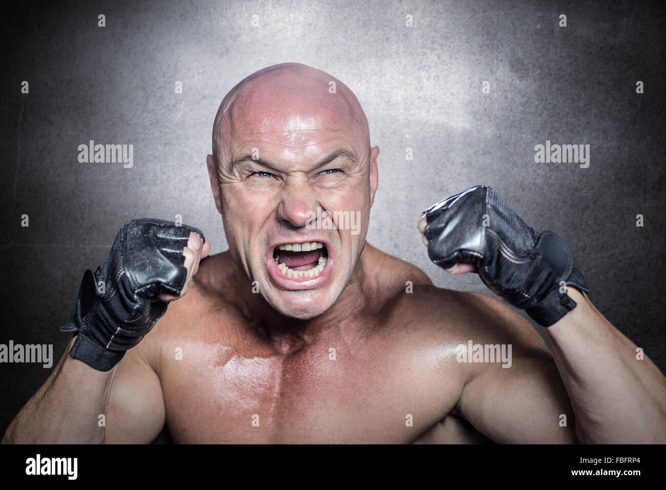 Composite image of angry fighter with gloves - Stock Image