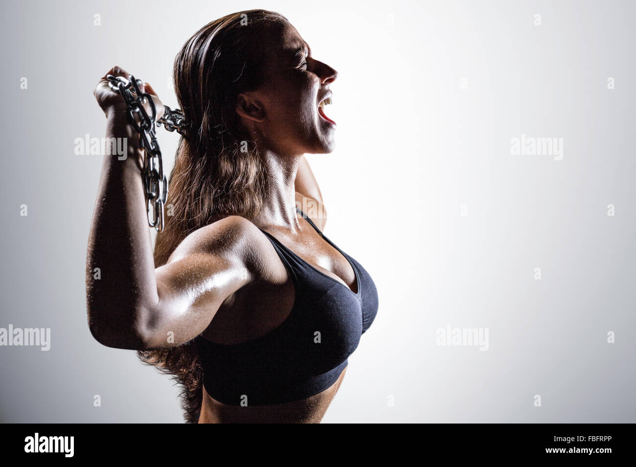 Composite image of side view of angry athlete shouting while holding chain - Stock Image