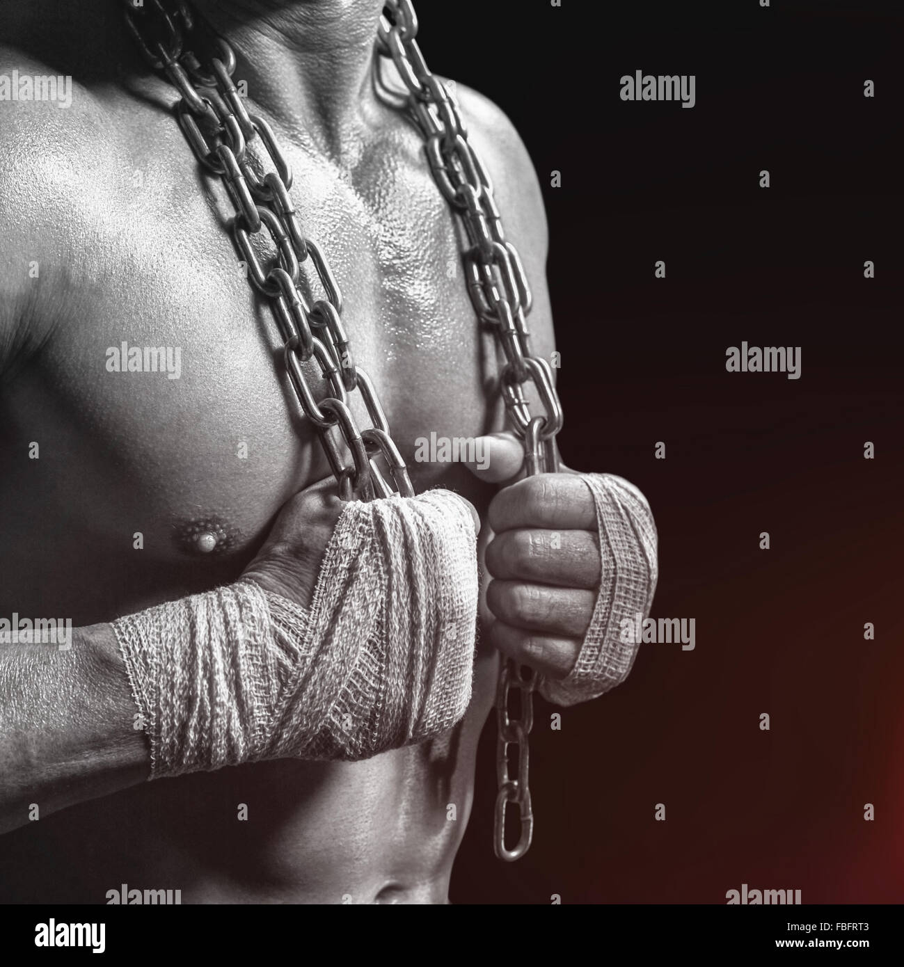 Composite image of midsection of bodybuilder holding chain - Stock Image