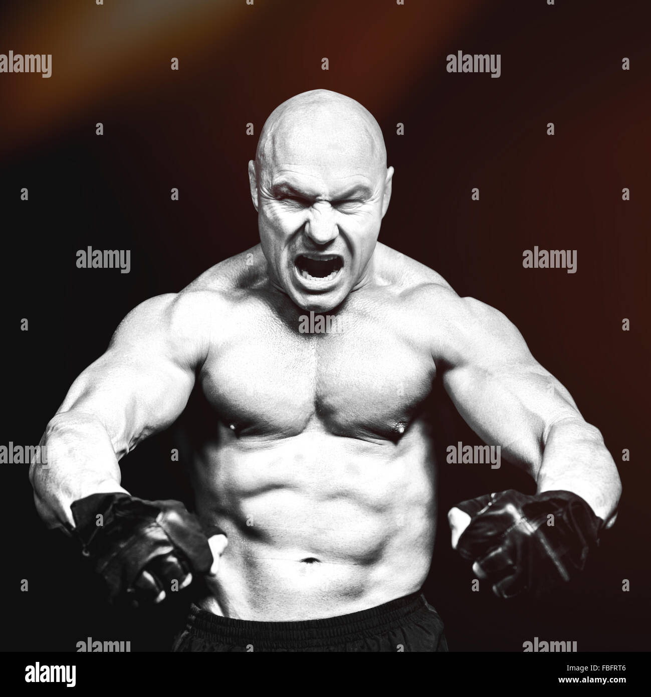 Composite image of aggressive fighter flexing muscles - Stock Image