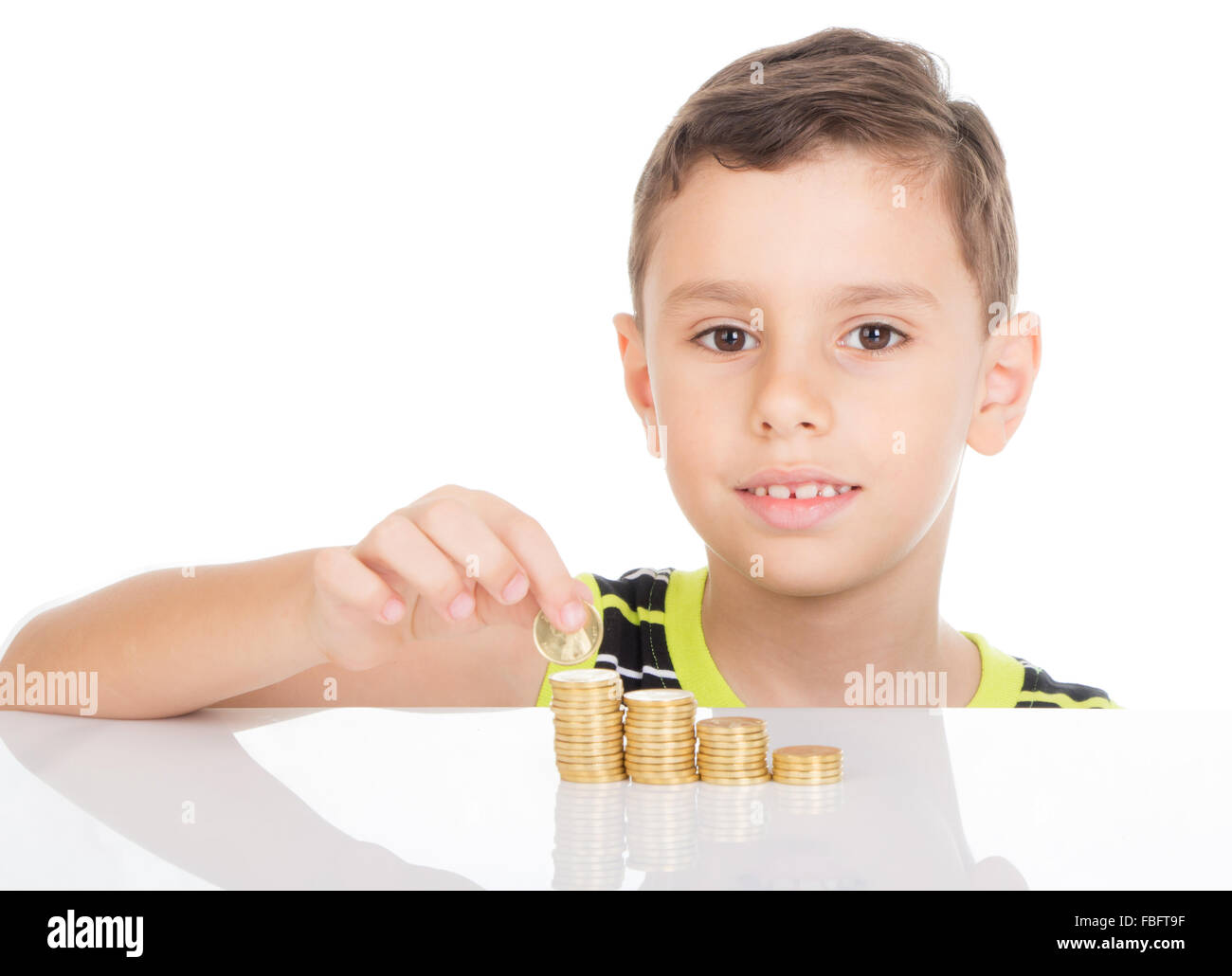 Kid building towers with his golden coins - Stock Image
