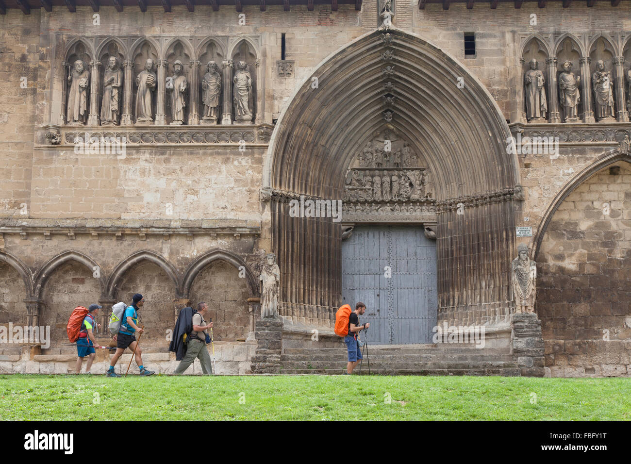 Pilgrims passing the Church of Holy Sepulchre as they enter the village of Estella-Lizarra - Navarre, Spain. - Stock Image