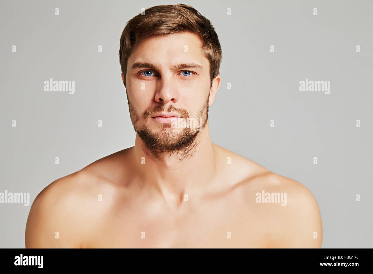 Portrait of a serious young man with bare shoulders on a gray background, powerful swimmers shoulders, beard, charismatic, - Stock Image