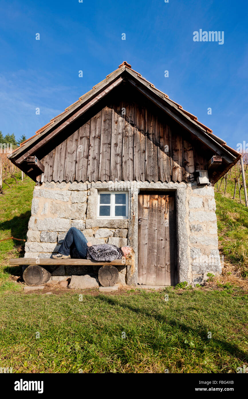 Woman basks in front of a small house Stock Photo