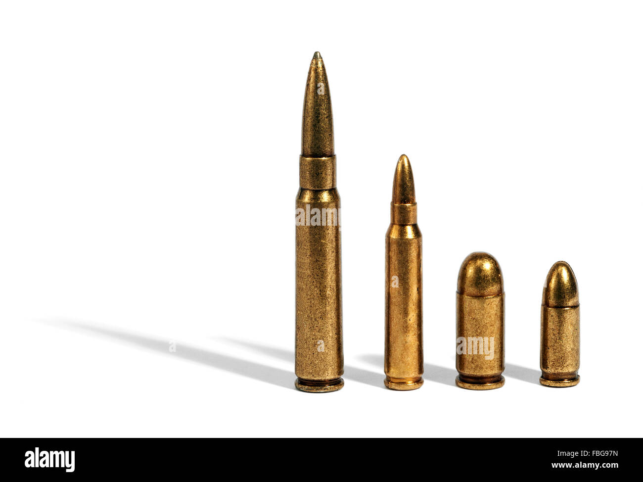 Four different sized bullets comparing ammunition over white background - Stock Image