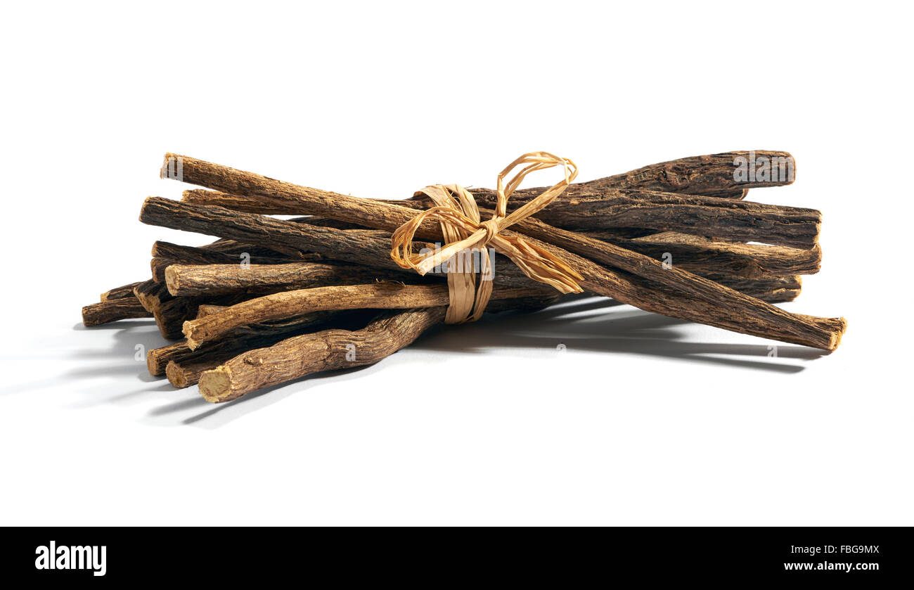Single bundle of cut and dry licorice root tied with string over white background - Stock Image