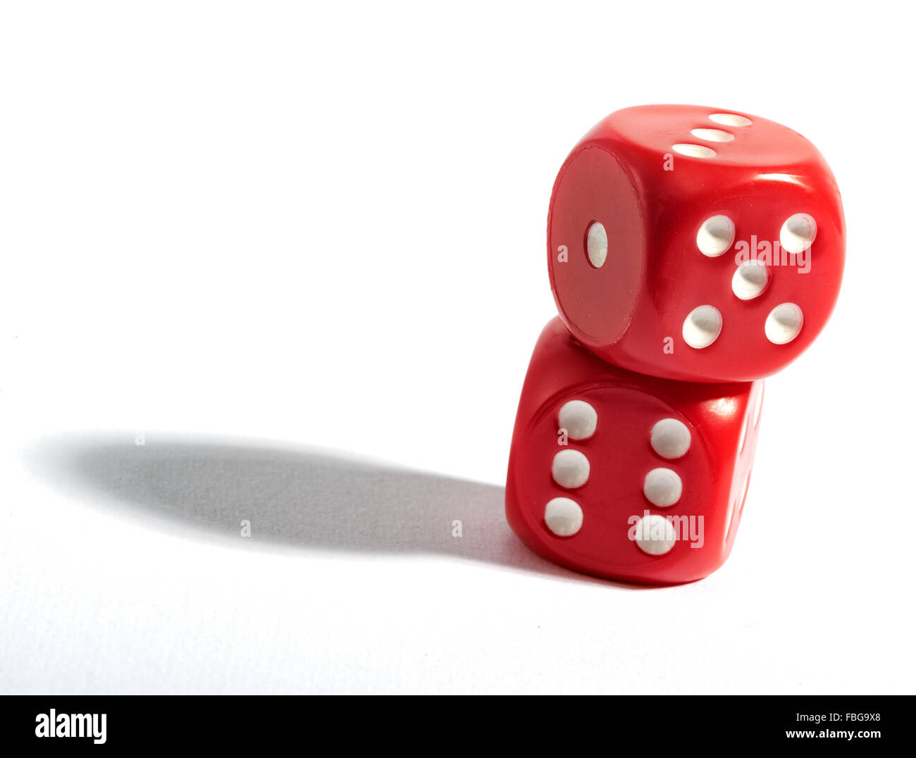 Two plastic red six sided dice stacked on top of each other over white background - Stock Image
