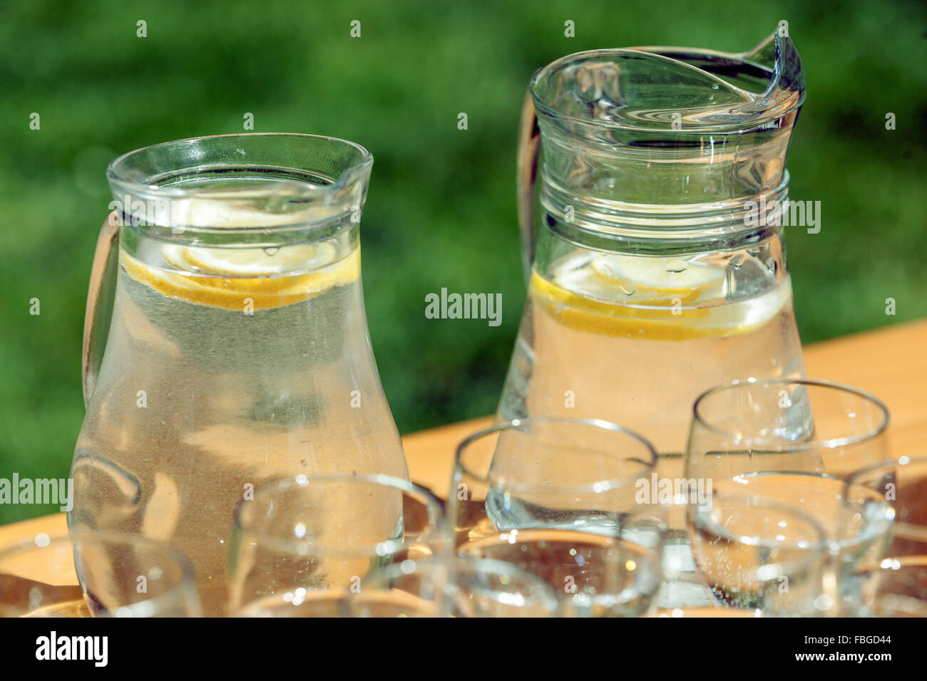 The two carafes of fresh lemon flavored water and glasses on a table in the garden - Stock Image