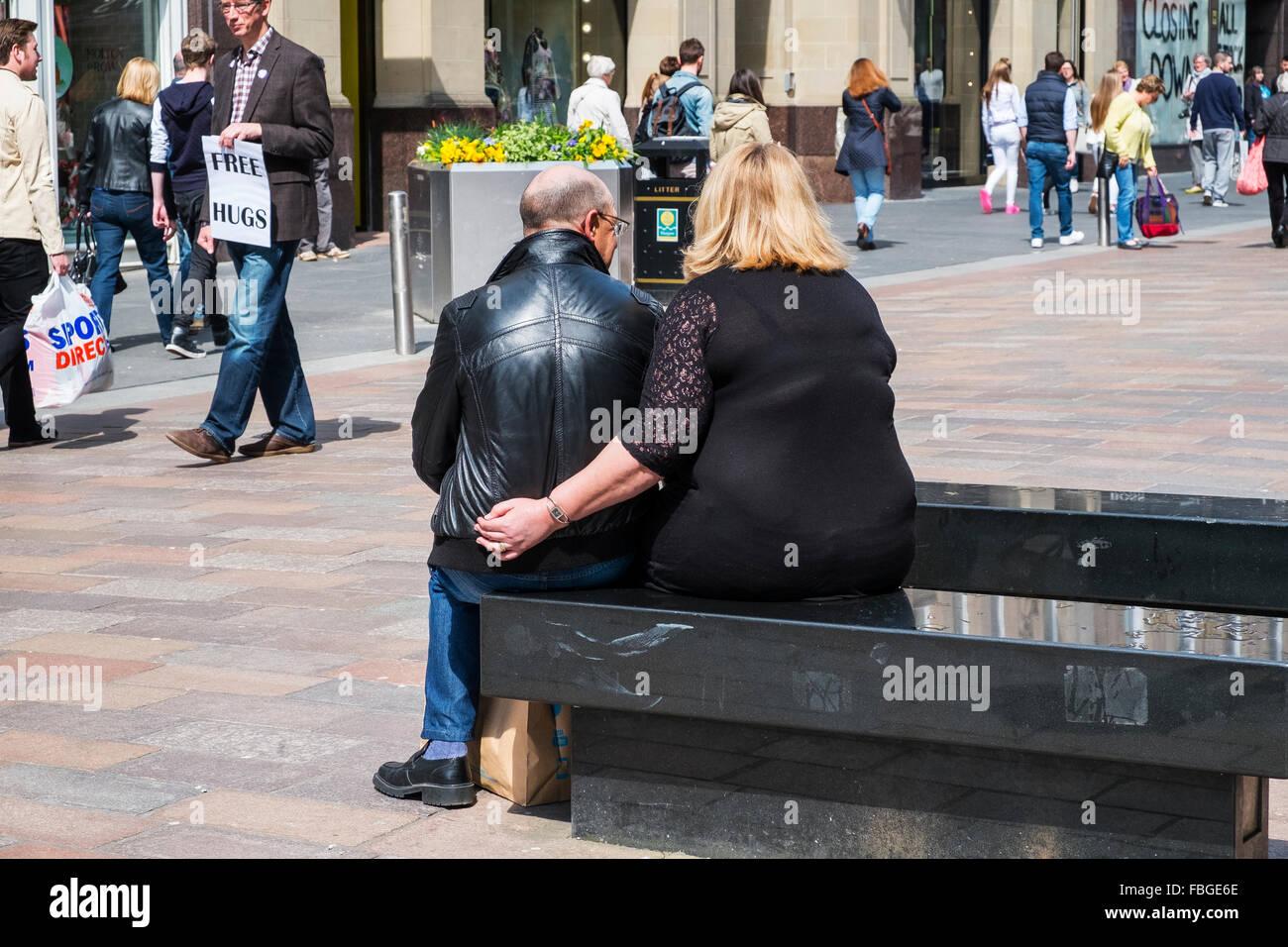 overweight loving couple sitting bench street uk - Stock Image
