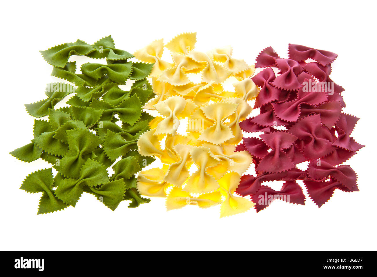 Dried pasta bows in the shape and colours of the Italian Flag on white background - Stock Image