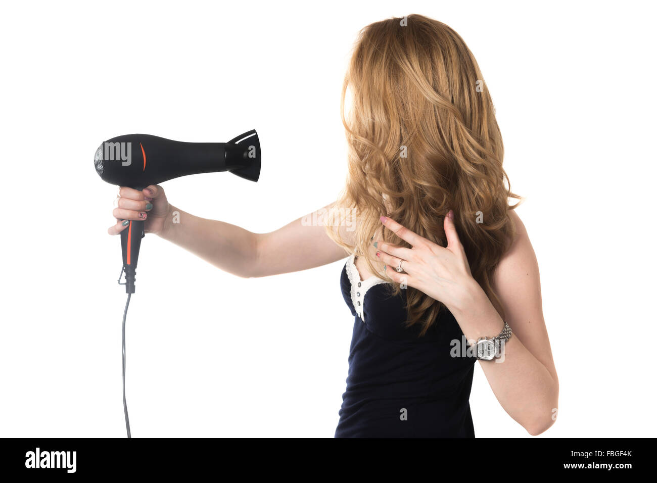 Young gorgeous blond Caucasian woman holding black hair dryer, styling her beautiful long hair, studio shot, isolated - Stock Image