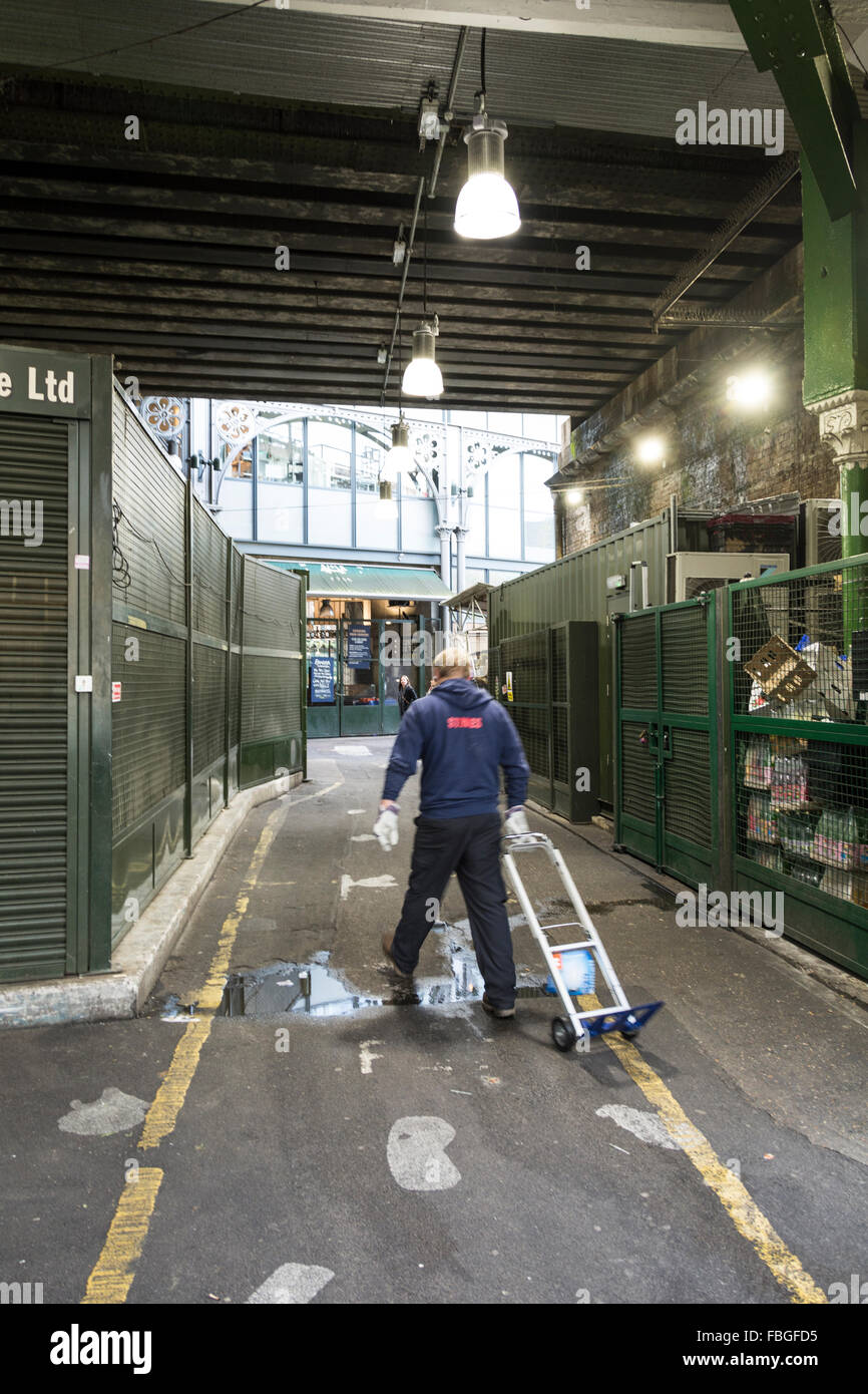 Market trader pulling his trolley in a deserted Borough Market in Southwark, London, UK - Stock Image