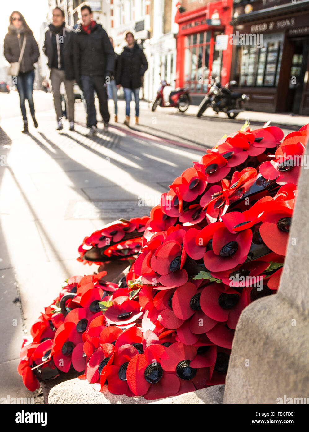 A wreath of red poppies laying in a London street commemorates the sacrifice of men and women in the first & - Stock Image
