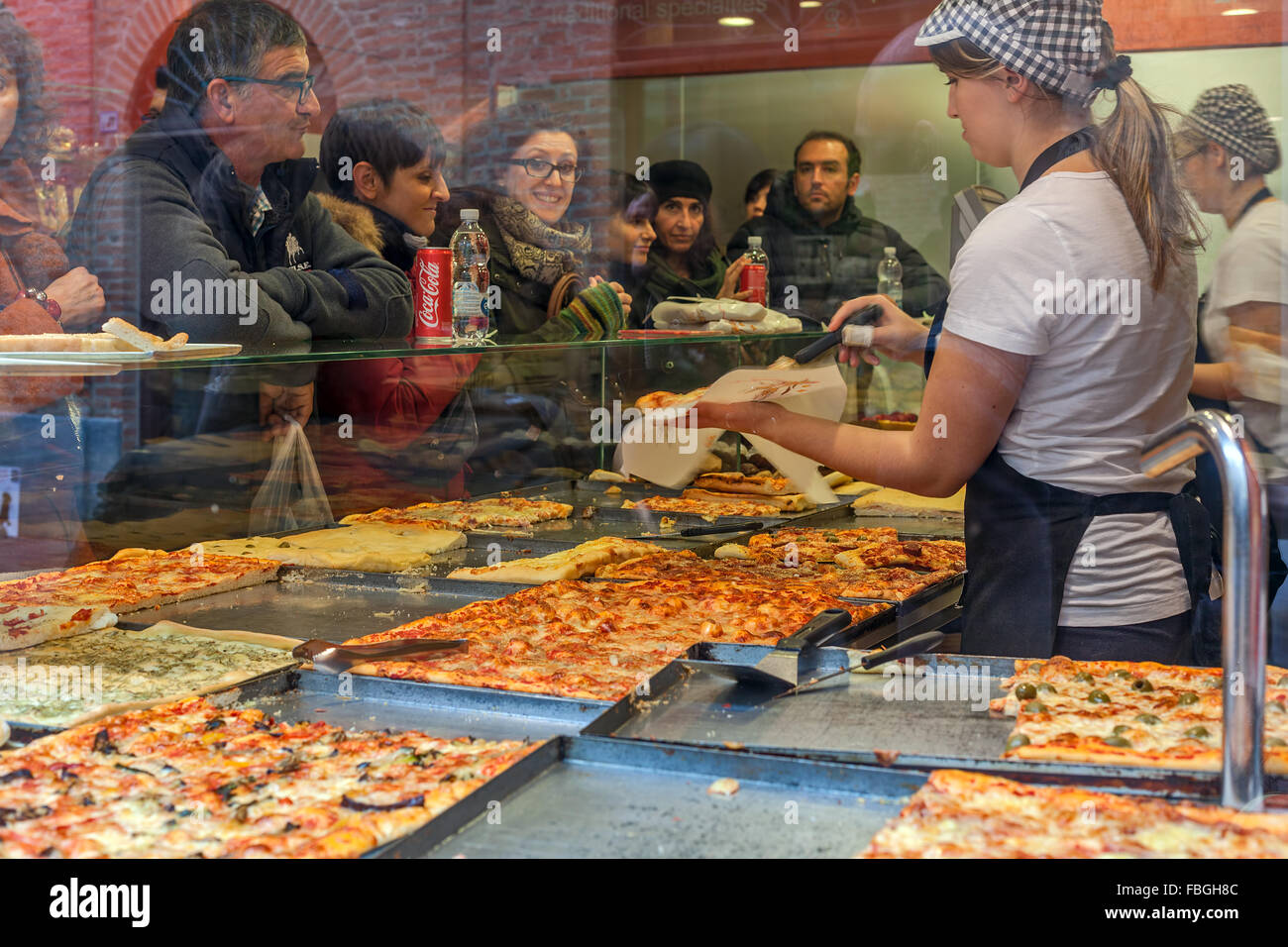 People inside typical pizzeria buying pizza in Alba, Italy. - Stock Image
