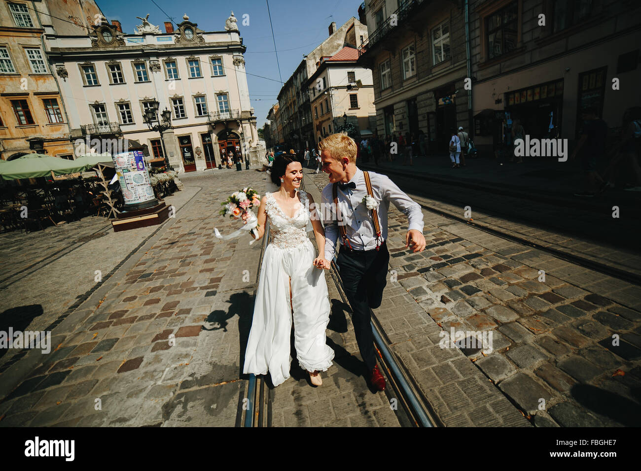 the bride and groom running along streets Stock Photo