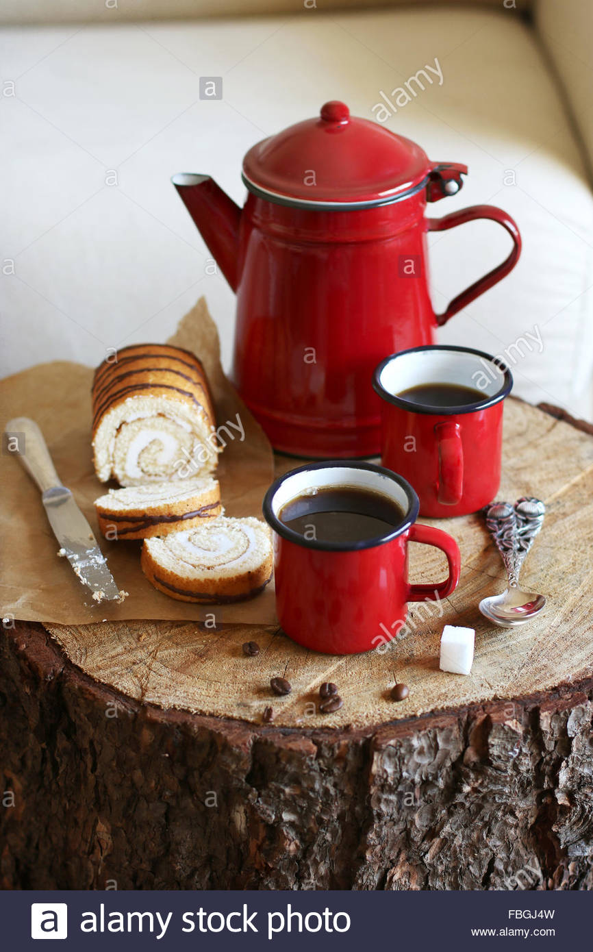 Enamel mugs with hot coffee and swiss roll cake - Stock Image