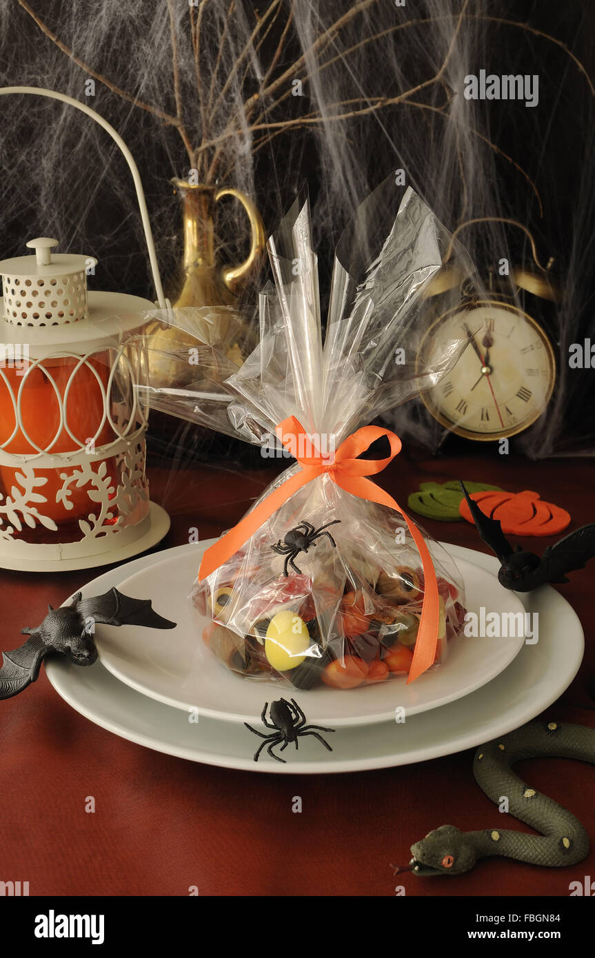 Sweets in the package on the festive table in honor of Halloween - Stock Image