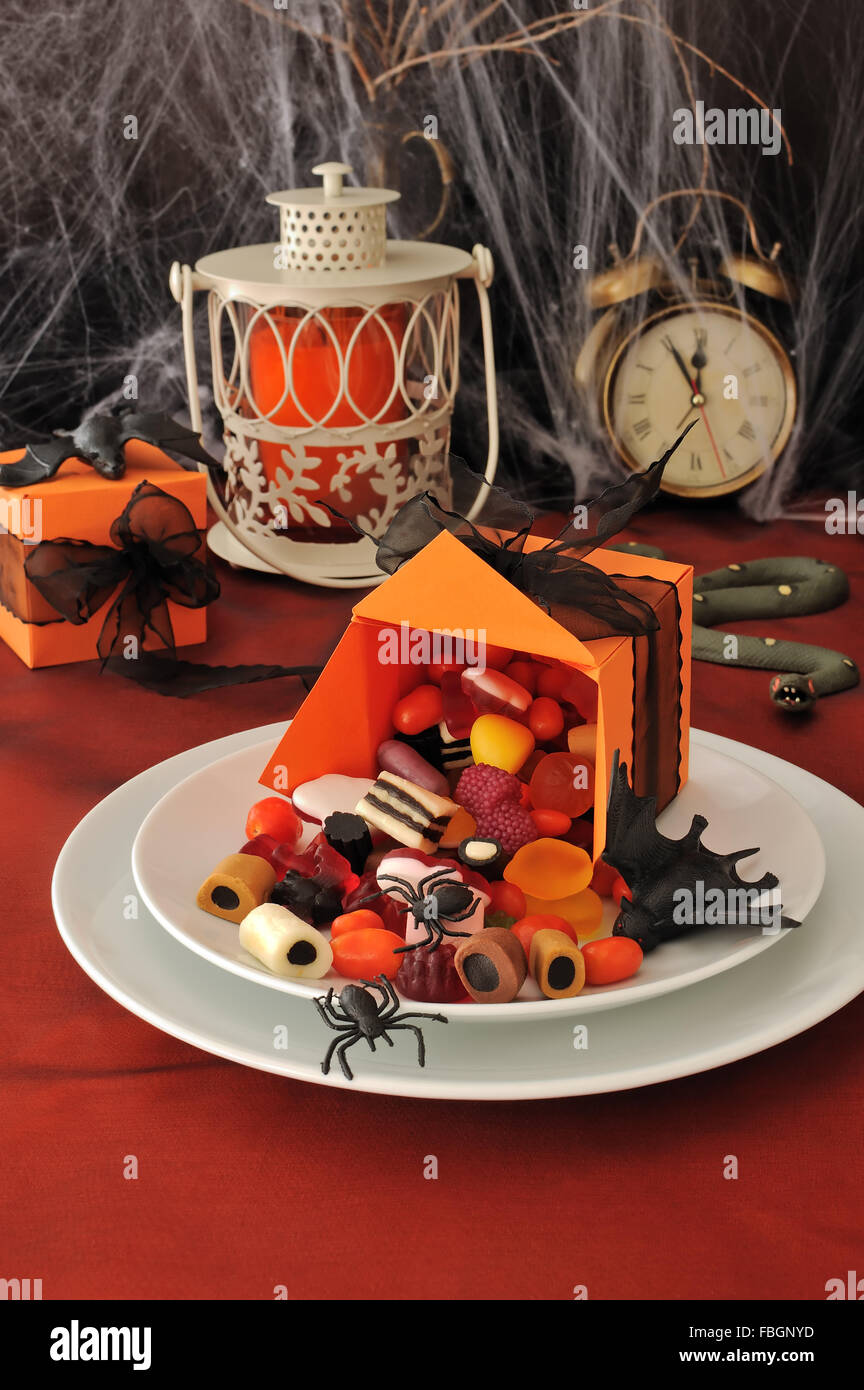 Spilled out of the box sweets on the holiday table in honor of Halloween - Stock Image