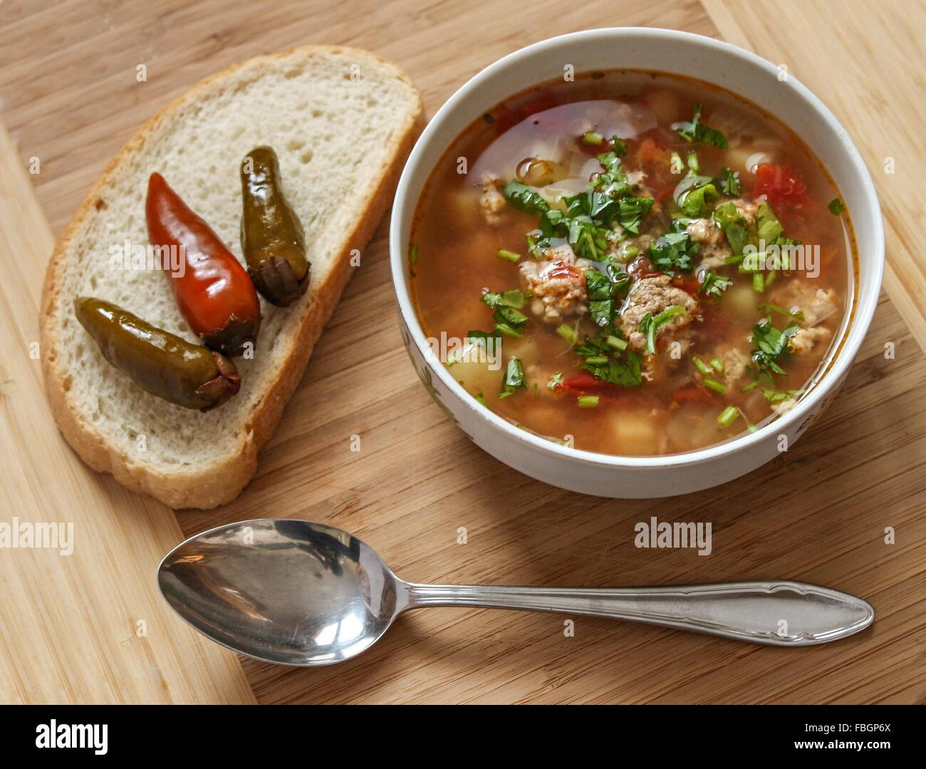 Food - Soup with meat balls with chili peppers and bread - wood background - Stock Image