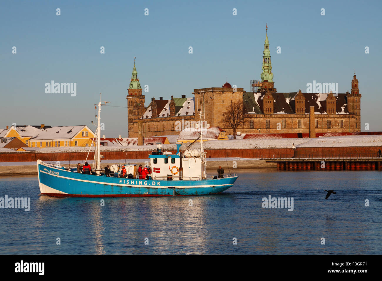 Anglers returning to Elsinore on a tour fishing boat after a day's fishing passing a snow covered Kronborg on a Stock Photo